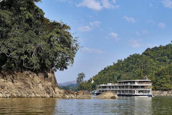 Skip på elven med bratte skåninger og trær. Foto.