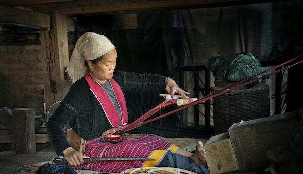 En eldre etnisk Palaung-kvinne fra East Shan State i Myanmar (Burma), som vever stoff med en enkel provisorisk vevstol.