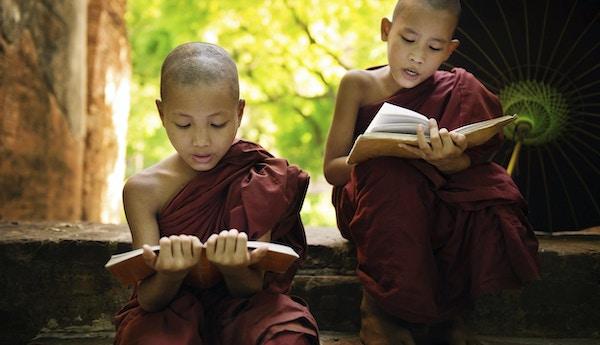 To unge munker i det Sørøst-asiatiske Myanmar sitter utenfor kloster og leser, buddhistisk undervisning.
