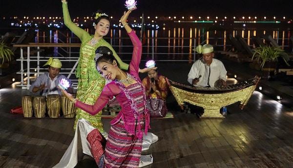 Soldekk i kveldsmørket med tradisjonelle dansere, lotusblomster og lokale instrumenter. Foto.