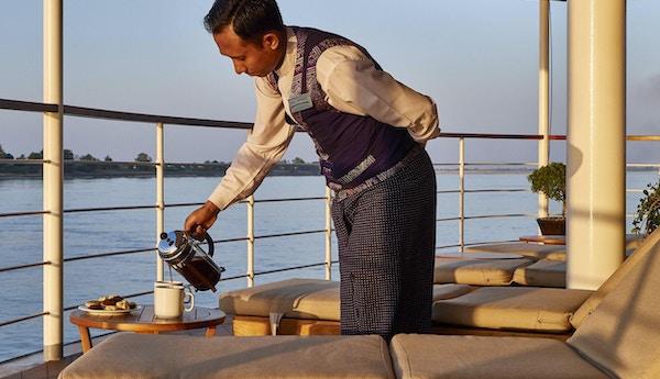 Kaffe serveres på soldekk med solsenger og utsikt over Irrawaddy. Foto.