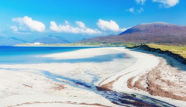 Luskentyre-stranden på vestkysten av Isle of Lewis. Hvit sandstrand med karrige fjell i bakgrunnen.