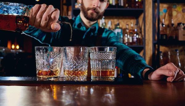 Barmannen skjenker whisky i tre glass.