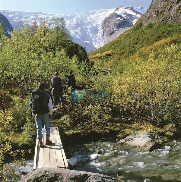 Personer som går på liten bro inn mot bre