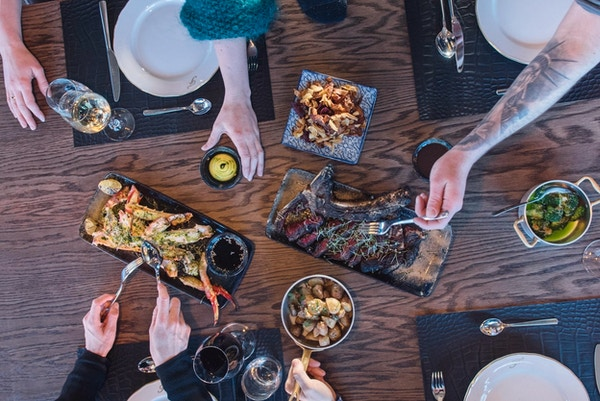 Fem matfatpå bordet der flere forsyner seg med mat på det dekkede bordet