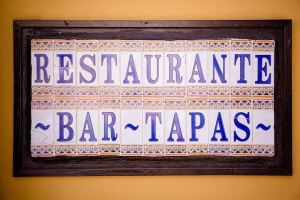 Rustikk keramikkskilt som reklamerer for en tapasrestaurant og bar, spansk mat