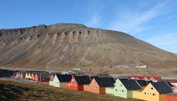 Hus i rekker i ulike pastellfarger som har fjellet i bakgrunnen