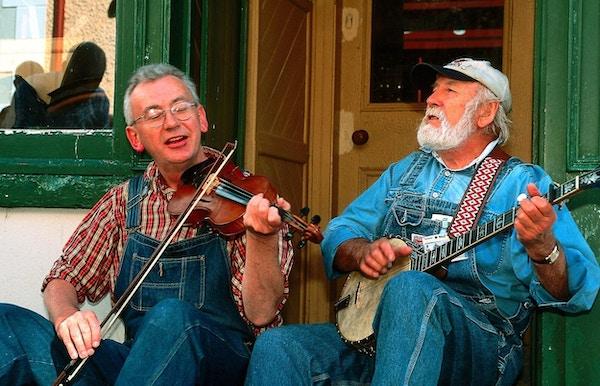 to irske musikere utenfor en pub, en spiller fele og den andre banjo