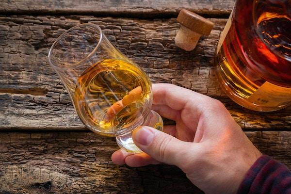 hånd holder whisky i et glass for å smake på en trebakgrunn