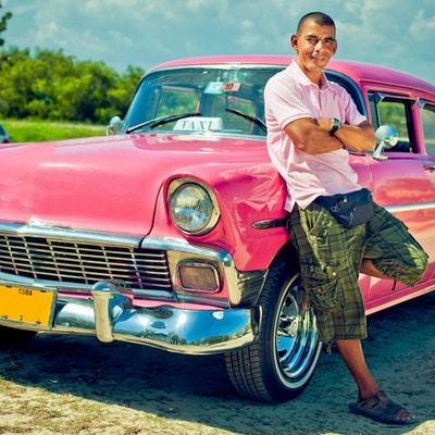 Taxisjafør som poserer med sin retrobil