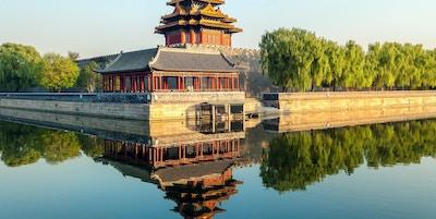 Nordvesthjørnet av den forbudte by som reflekteres over vann. Trær som omgir hjørnet og klar himmel .; Beijing, Kina