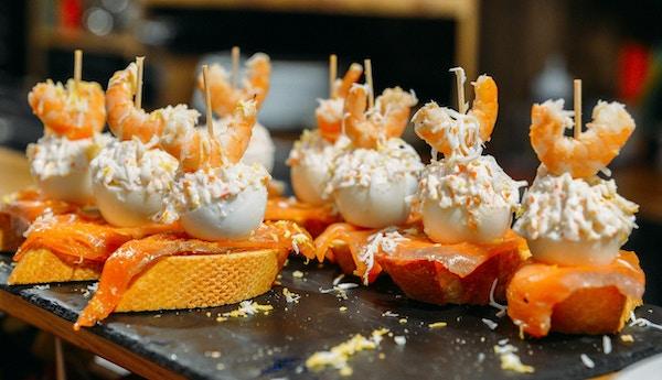 Spanske tapas kalt pintxos fra Baskerlandet serveres på en bardisk i en restaurant i San Sebastian, Spania