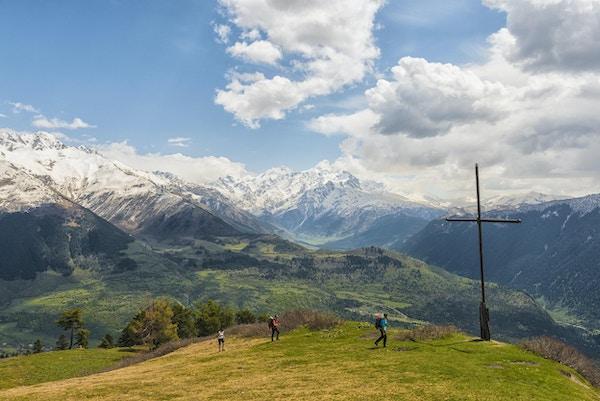 Visning med høy vinkel på Mestia-fjellet, som ligger høyt oppe i landsbyen Mestia, i Samegrelo-Zemo Svaneti-regionen. Hvert hus hadde til tider sitt eget forsvarstårn, men i dag står det fremdeles noen dusin. Tre turister går til det store korset som markerer toppen av Mt. Mestia. Det er en grønn bakke foran, i bakkekuler over landsbyen mot fjellkjeden i Nord-Kaukasus. Toppene er dekket av snø under en blå himmel.
