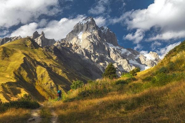 Landskap med fjellet Ushba i solnedgangslys og turist