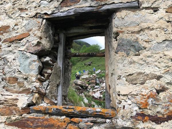 Fjellvandrere sett fra et vindu i en gammel steinhytte