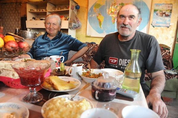 Besøk i Kits jkhøldæsj ei lita svansk byg. Maria og Valer  sitter ved bordet med hjemmelaget mat