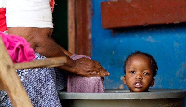 En gammel bestemor fra Xhosa gir barnebarnet sitt et bad i Sør-Afrika på verandaen til deres gamle hjem.