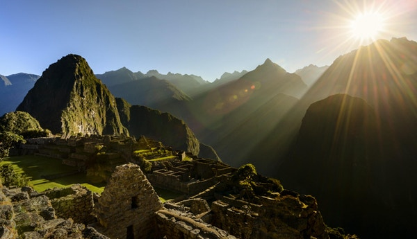 Sol som stiger over fjellene ved Inka-ruinene i byen Machu Picchu, Peru. Sola slår Wayna Picchu-fjellet med utsikt over byen.