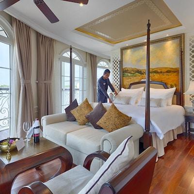 Suite med tregulv, dobbelseng, stol, bord, store vinduer og en som rer opp sengen. Foto.