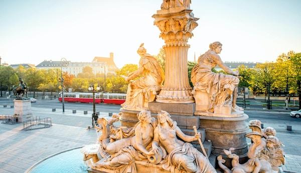 Athena- statue nær parlamentbygning med Wiens bybilde og en gammel trikk i bakgrunnen ved soloppgangen