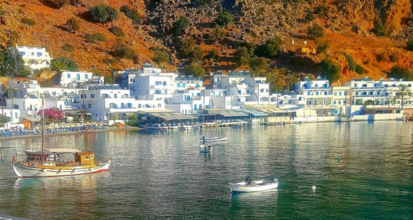 Fiskebåt og den naturskjønne landsbyen Loutro på Kreta, Hellas