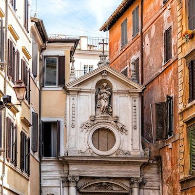 Inngangen til liten kirke i enden av gate i Roma