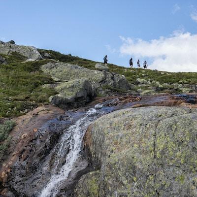 Bekk i fjellet med turgåere i bakgrunnen.