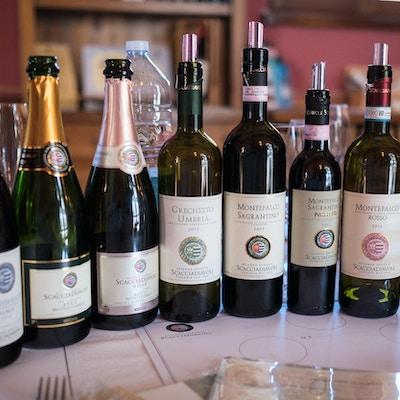 syv flasker vin på et bord