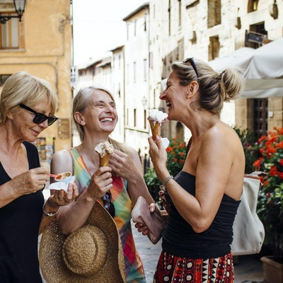 Tre venninner som står og spiser italiensk iskrem mens de står i en gate i Toscana om sommeren. De smiler og vender seg mot hverandre mens de nyter ferien.