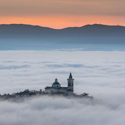 Utsikt over Trevi i Umbria (Italia) ved solnedgang med tåke.