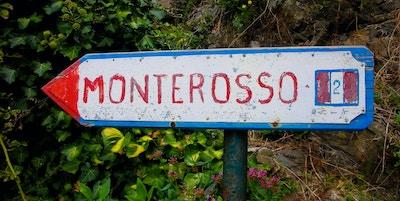 Et skilt som peker til den lille landsbyen Corniglia, Italia på kysten av Cinque Terre 15. august 2014. Denne stien gjennom nasjonalparken Cinque Terre fører deg gjennom vingårder og sitronfrukthager på en bratt bakkeside med utsikt over havet .