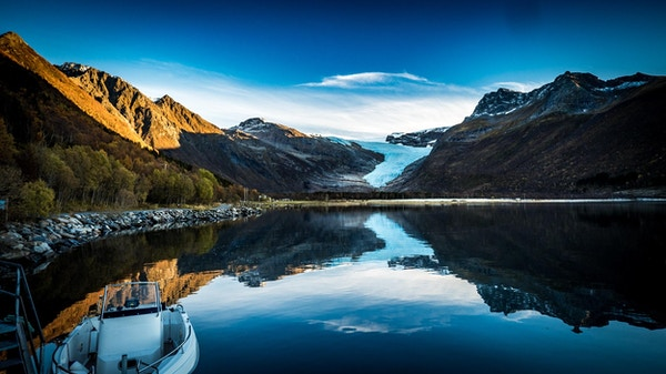 Landskap med fjell og vann og en isbre lengst borte, en båt i forgrunnen.