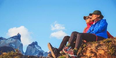 To personer på fottur sitter på en klippe og nyter storslått natur, Patagonia