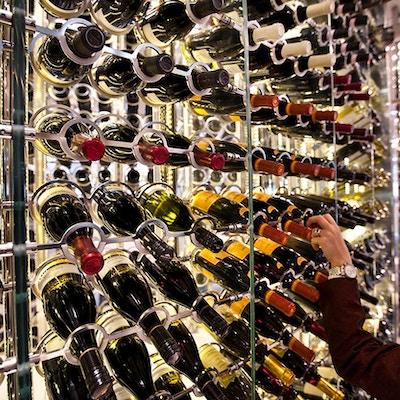 En jente velger en rødvin fra vintårnet i restauranten