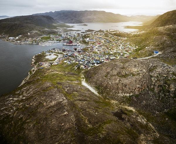Qaqortoq, liten landsby på Grønland ved kysten. Luftfoto av hus i solnedgangen i en liten by ved kysten.