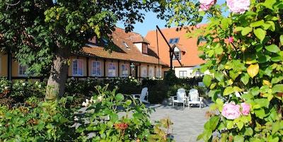 Roser og busker utenfor hus med stoler og bord