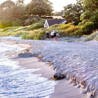Mennesker går på sandstrand om sommeren