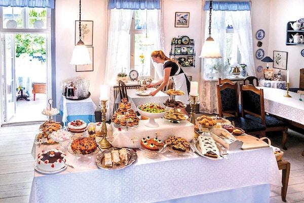 Bord med mange ulike kaker i hyggelig gammeldags cafe