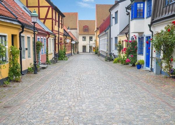 Brosteinsbelagt gate og fargerike hus i gamlebyen i Ystad, Sverige.