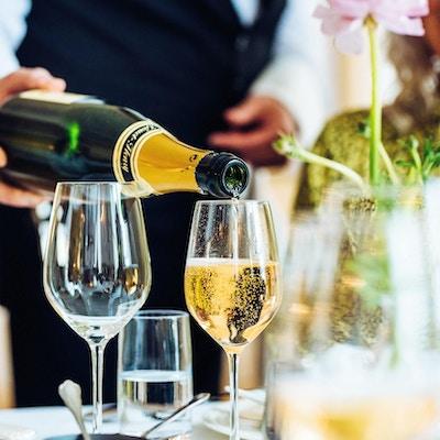 Kelner heller musserende vin i glass på restaurant.