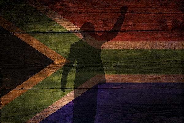 Et Sør-Afrikansk flagg på en grungeinspirert bakgrunn med et skyggeoverlegg for frihet.