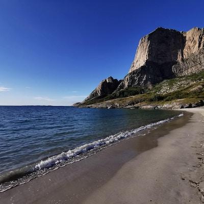Sandstrand og hav med fjelltopp i bakgrunnen.