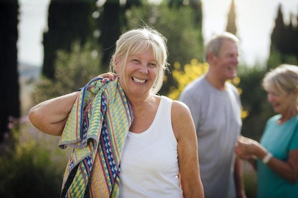 Kvinne som tar en pause fra en treningsklasse utendørs på en solrik dag. Hun smiler mens hun ser på kameraet og holder et håndkle til nakken. Eldre par er i bakgrunnen, men ute av fokus.