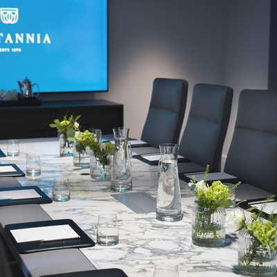 Møterom med konferansebord og stoler rundt og storskjerm