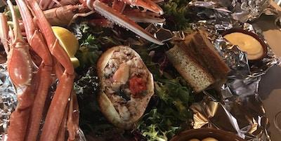 Lekkert anrettet på folie sjømat med krabbe, sjøkreps, reker, brød, sitron og alioli