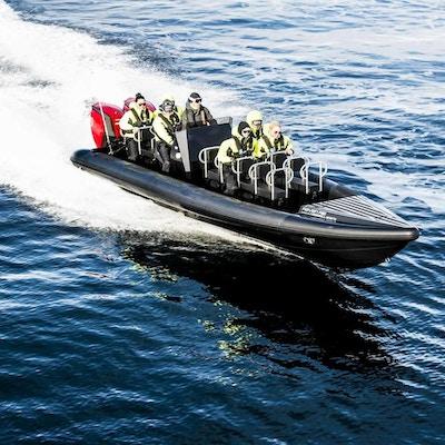 Mennesker ombord i en rib kjørende i høy fart på havet