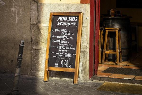 Et tavle utenfor en Madrid-restaurant tilbyr en smaksmeny med typiske tapasretter til en fast pris.