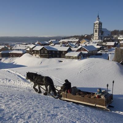 Hest og slede i vinterterreng med kirke og småhusbebyggelse i bakgrunnen
