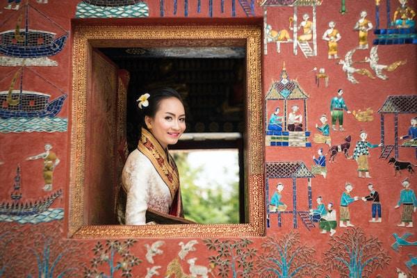 Foto av en vakker Laos-dame i tradisjonelt kostyme som smiler, og ser ut av et vindu fra et tempel (Wat Xieng Thong) i Luang Prabang. Fokus på ansiktet hennes og mykt fokus på området rundt.