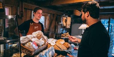 Bakervarer til salgs i gårdsbutikk med en kunde og en ekspeditør